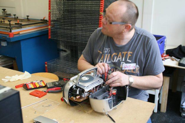 Eine Elektrofachperson repariert einen CD-Player